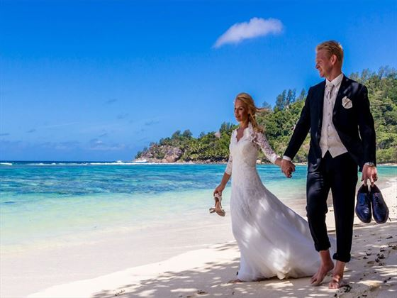 Bride & Groom hand in hand at Kempinski Seychelles Resort