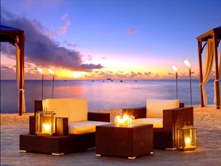 Beachfront seating at sunset at The House by Elegant Hotels