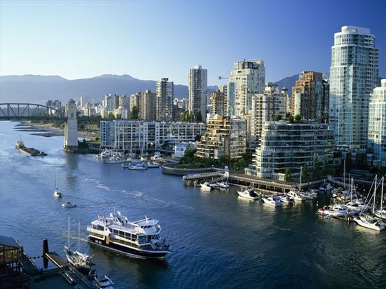 A boat cruises past a marina and downtown buildings on False Creek, Vancouver