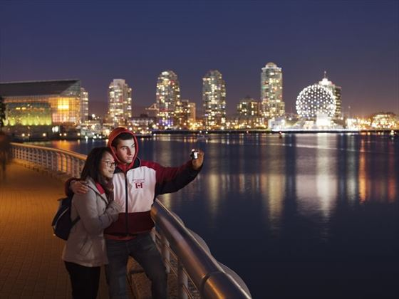 Couple on False Creek seawall at night with view of the Telus World of Science, Vancouver