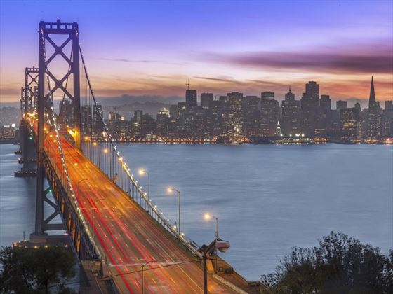 View of Bay Bridge and San Francisco skyline at sunset
