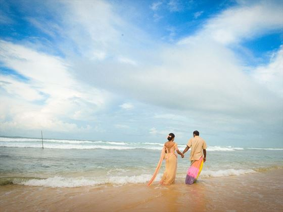 Lovers stroll on the beach at The Fortress