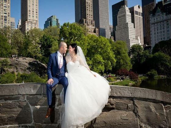 The happy couple sitting on Gapstow Bridge, Central Park
