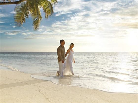 Lovers walking in the water at Desroches
