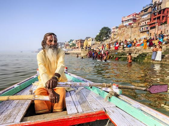 Sadhu rowing a boat in Varanasi