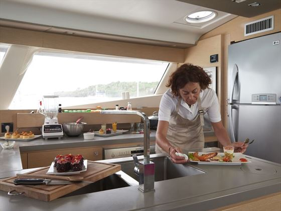 Steward/cook cooking up a feast on board the Sanya 57