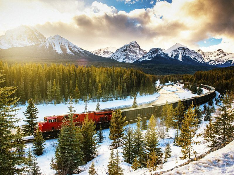 canadian pacific rail train heading through banff national park in winter