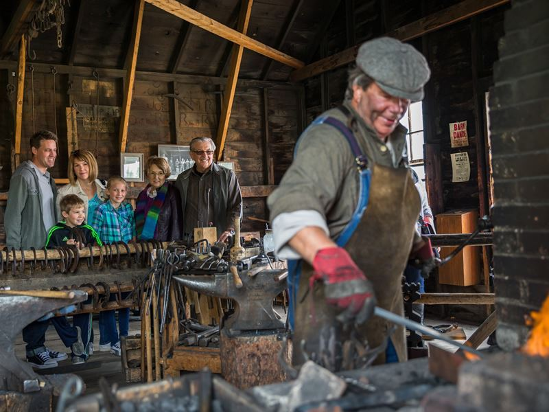 family watching a blacksmith at heritage park in calgary